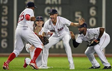 As outfielders Rajai Davis (25), Andrew Benintendi, and Jackie Bradley Jr. did their Win, Dance, Repeat celebration, relief pitcher Joe Kelly (center) photobombed them as he ran in from the bullpen to join the party.